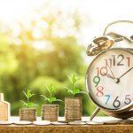 Oszczędzanie w domu za pomocą taryfy G13. Trzy stosiki monet, obok zegar typu budzi oraz drewniana figurka domu